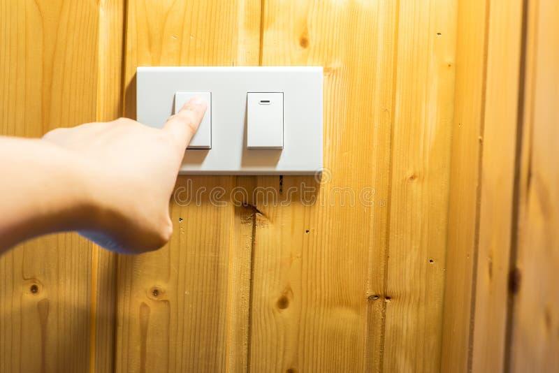 Palcowa prasa na lekkim przełącznikowym guziku przy drewnianą ścianą fotografia royalty free
