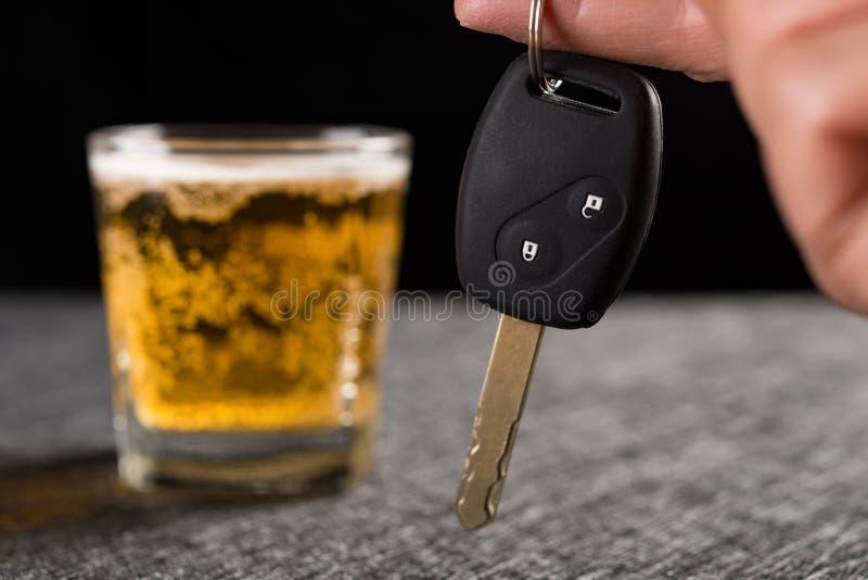 Palcowy chwyt samochodowy klucz przed filiżanką piwo fotografia stock