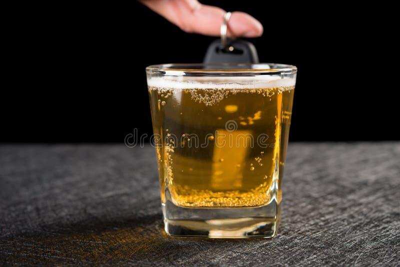 Palcowy chwyt samochodowy klucz za filiżanką piwo zdjęcia royalty free