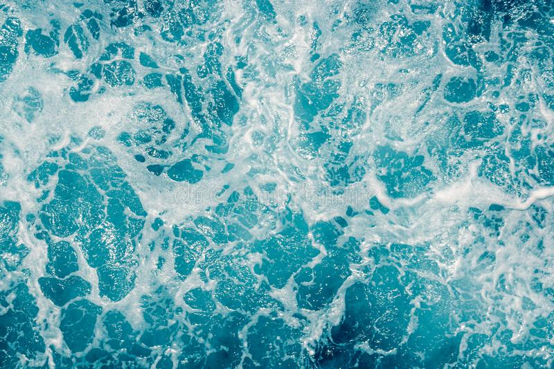 Pale blue green sea surface with waves and foam, abstract background.  royalty free stock photo