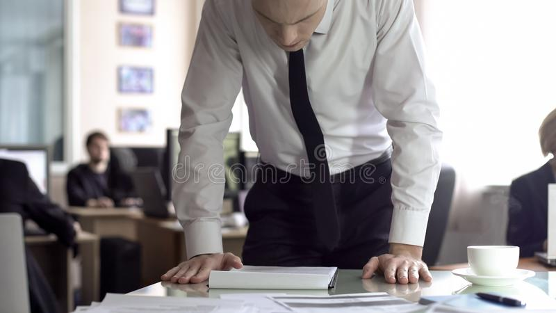 Pale businessman reading contract, worrying about loss of company revenue royalty free stock photo