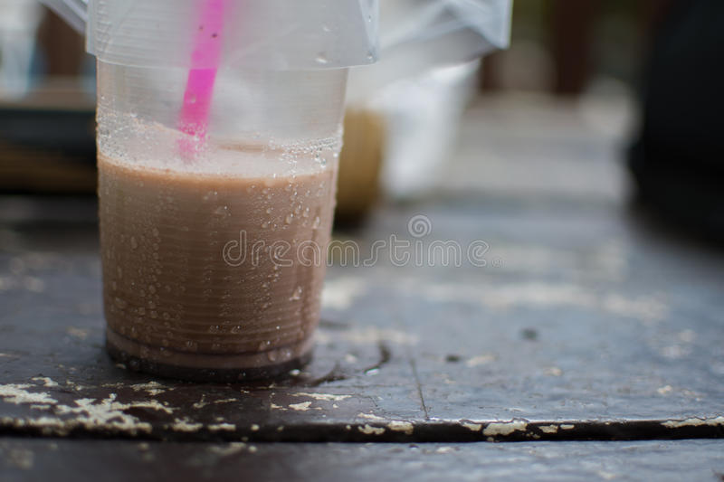 A pale coffee in side a plastic glass on a wood table. royalty free stock photo