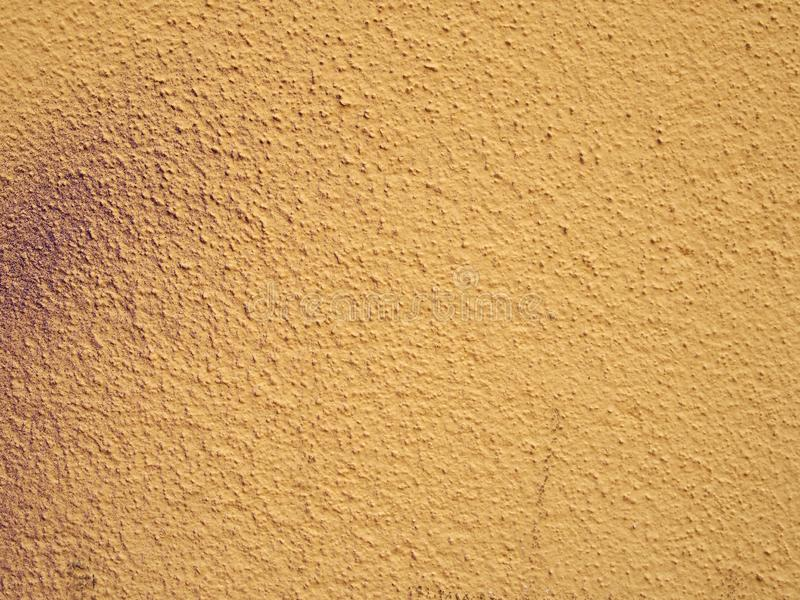 Pale grainy textured yellow wall background with hints of messy purple spray paint. A pale grainy textured yellow wall background with hints of messy purple stock photo