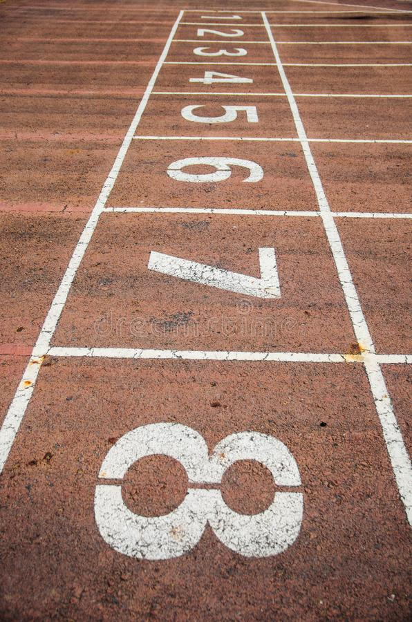 Pale red running track with number stock images