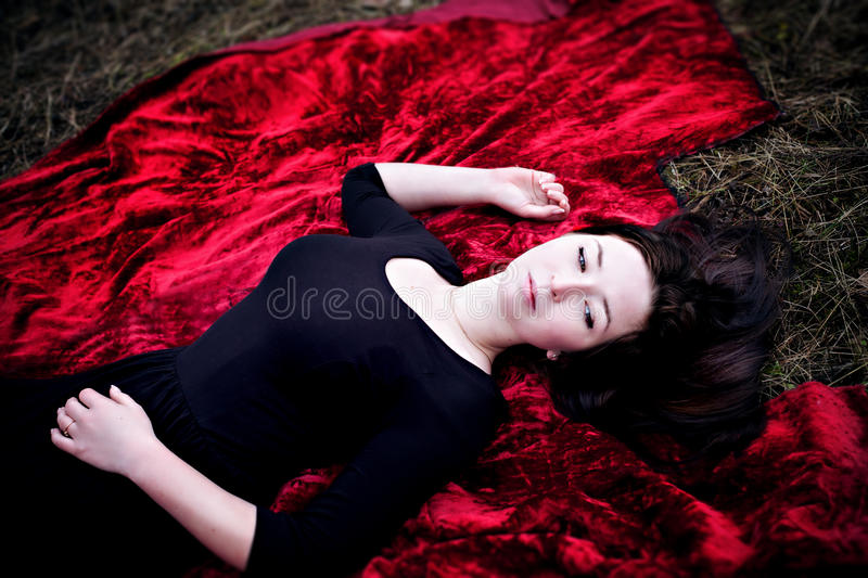 Download Pale Woman In Black Dress Lying On Red Carpet Stock Image - Image: 35447827