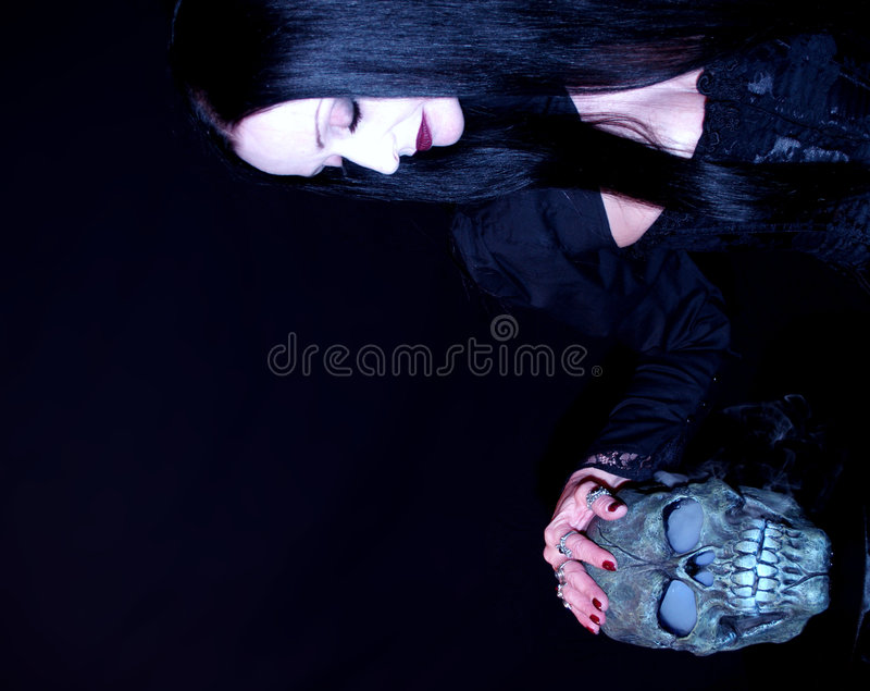 Pale woman with skull. Halloween theme with a woman and a steaming skull stock photography