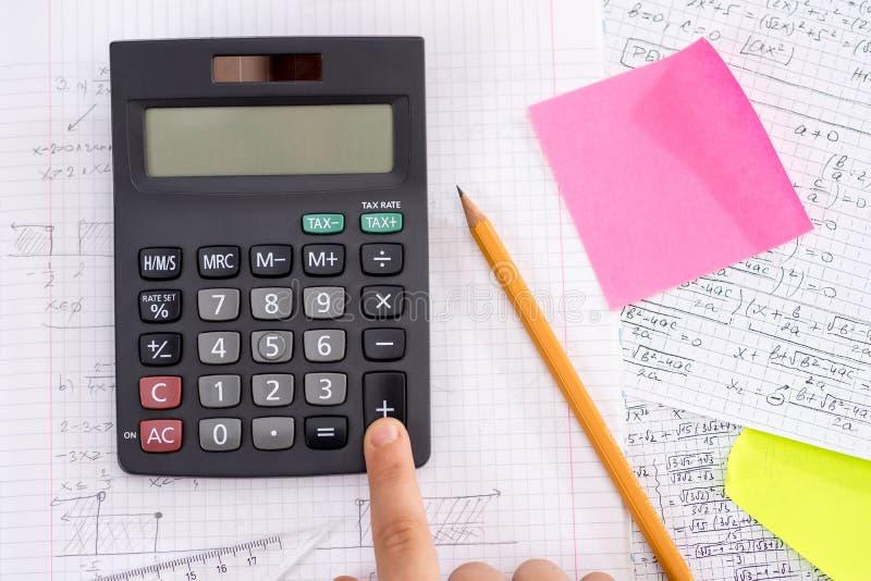 Palec na kalkulatora guziku Podczas Matematycznie lekcji zdjęcia stock