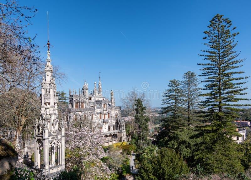 Paleis Quinta da Regaleira in Sintra op een duidelijke Zonnige dag tegen een blauwe hemel en lange groene bomen stock afbeelding