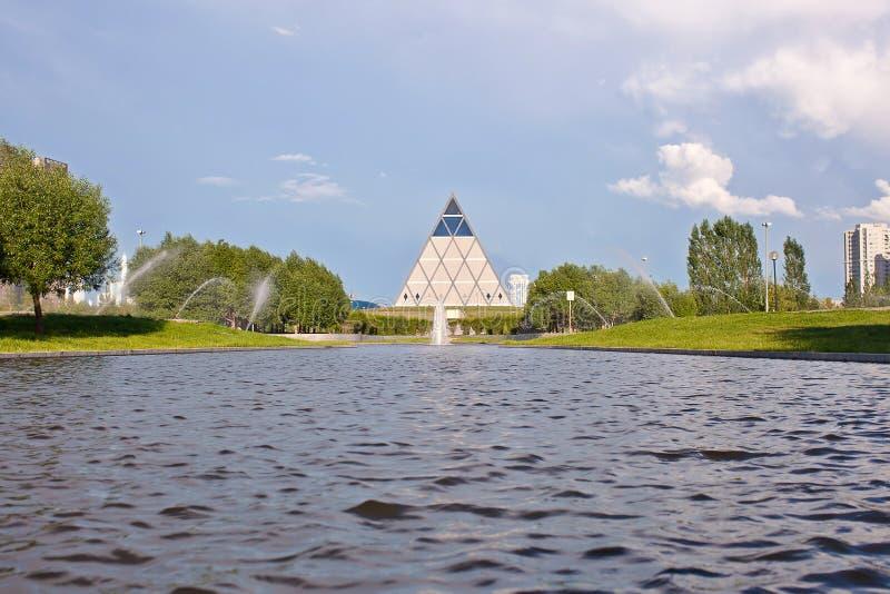 Paleis van Vrede en Overeenstemming - Piramide (Astana, Kazachstan) met water op voorzijde stock foto