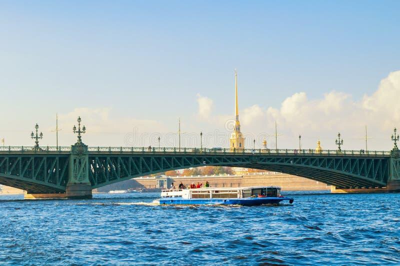 Paleisbrug en plezierboot bij de vestingsklokketoren van Neva River en Peter en van Paul op de achtergrond in St. Petersburg royalty-vrije stock afbeelding