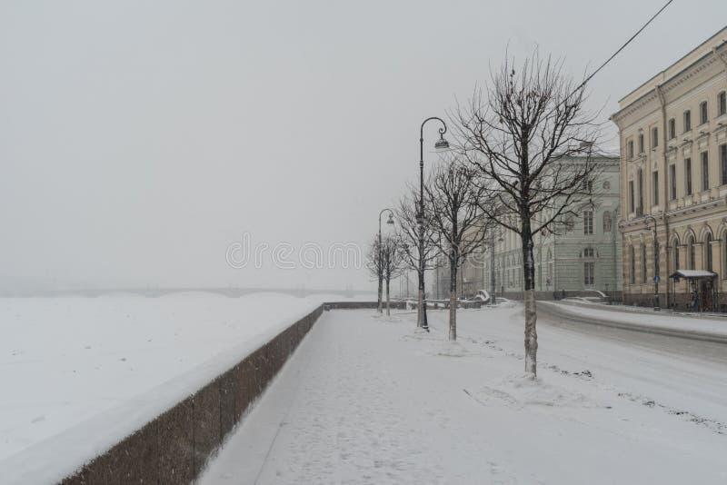 Paleisdijk en Kluisbrug in sneeuwval De winter in St Petersburg royalty-vrije stock afbeeldingen