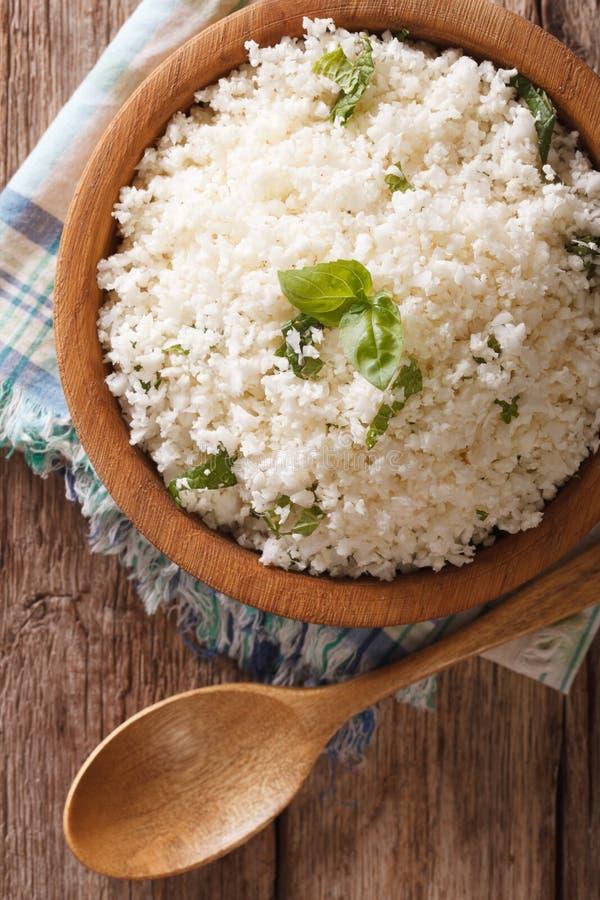 Paleo食物:与草本特写镜头的花椰菜米 垂直的名列前茅v 库存图片