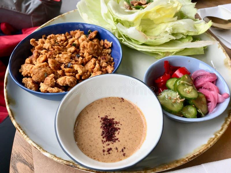 Paleo饮食食物鸡片断用海鲜酱和黄瓜沙拉和包裹用莴苣/鸡Wranch包裹 免版税库存照片
