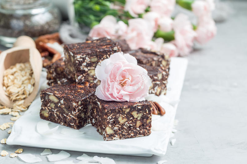 Paleo chocolate energy bars with rolled oats, pecan nuts, dates, chia seeds and coconut flakes, copy space royalty free stock photo