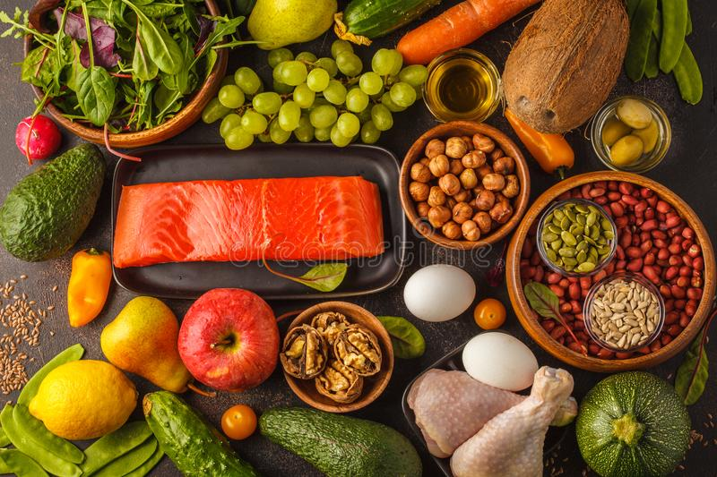 Paleo diet concept. High protein food. Fresh raw vegetables, fruits, meat, fish, top view. Paleo diet concept. Balanced food frame background. Copy space, dark stock image