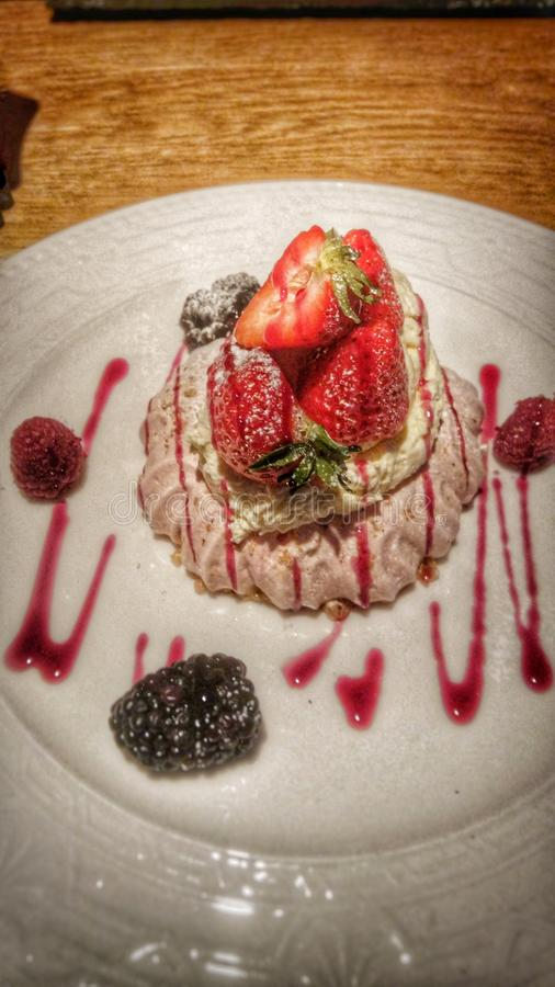 Paleo Diet meringue with fruit and raspberry sauce. A delicious Paleo Diet (caveman, paleolithic, primal diet) meringue with wiped cream, strawberries stock photography