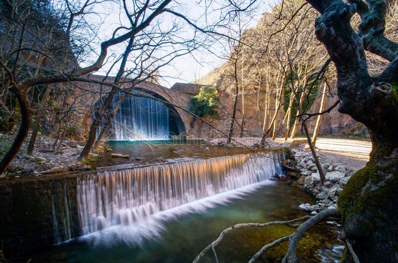 Paleokarya oude steen overspannen brug tussen twee watervallen De prefectuur van Trikala, Griekenland stock foto's