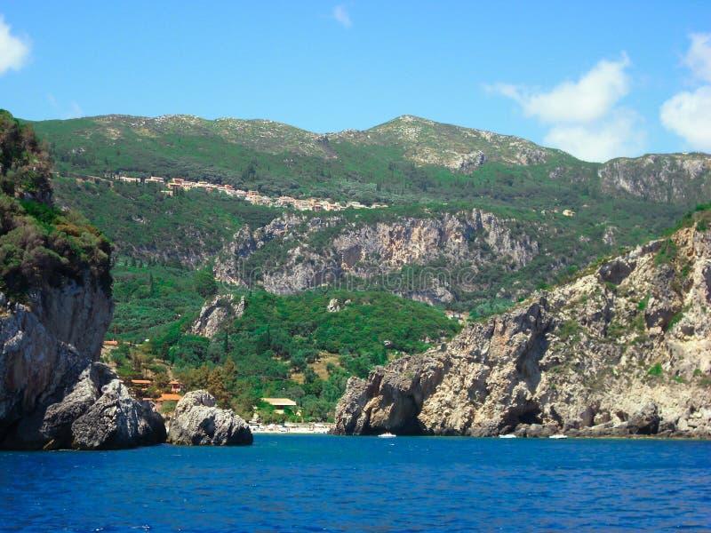Paleokastritsa i den Korfu ön, Grekland, stranden och steniga klippor som täckas i grön vegetation arkivbilder