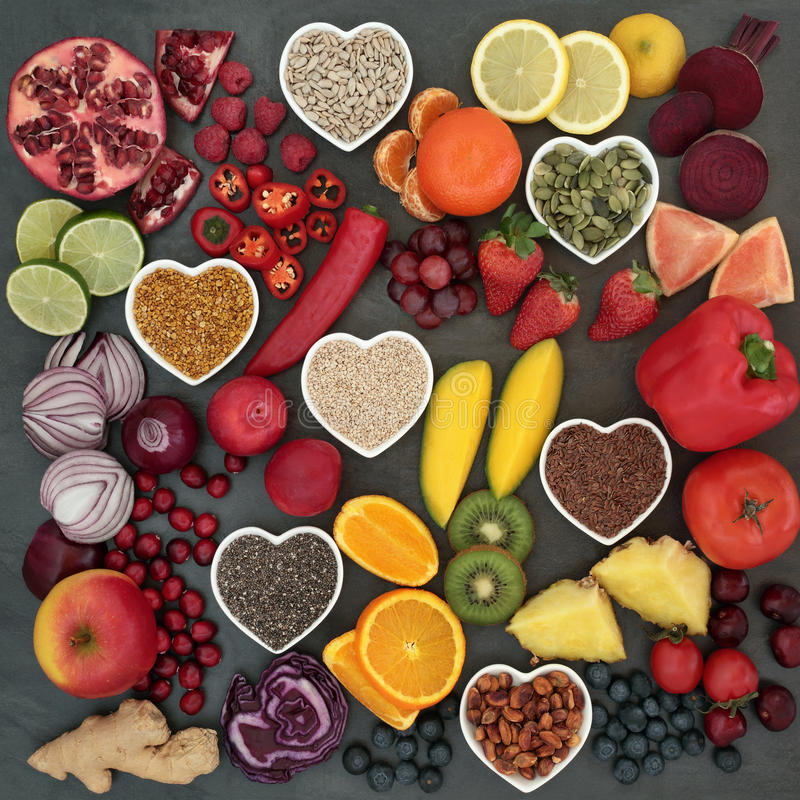 Paleolithic Diet Food. Of fresh fruit, vegetables, nuts and seeds on slate background. High in antioxidants, vitamins, anthocyanins and dietary fiber royalty free stock image