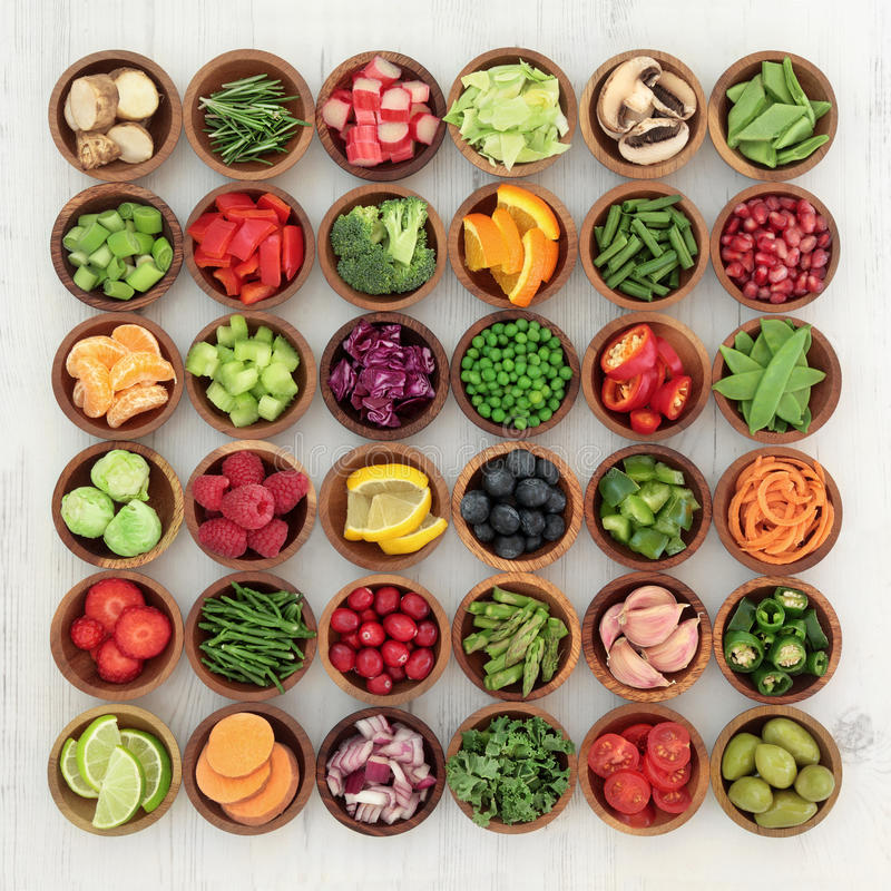 Paleolithic Diet Food. Paleolithic super health food of fruit and vegetables in wooden bowls over distressed white wood background. High in vitamins stock image