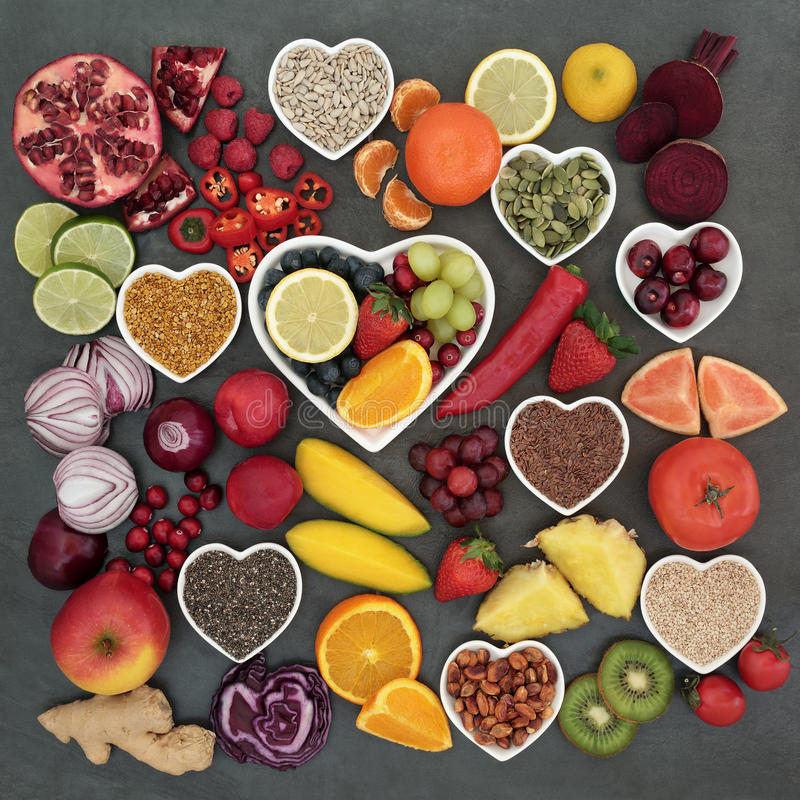 Paleolithic Health Food. Paleolithic diet health and superfood of fruit, vegetables, nuts and seeds in heart shaped bowls on slate background, high in vitamins royalty free stock images