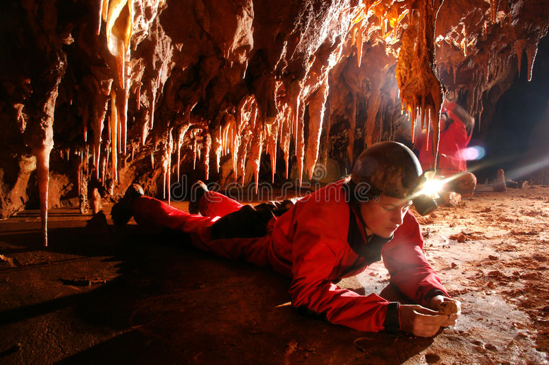 Paleontolgist studying fossils in a cave. A Paleontologist studying fossils in a cave stock image