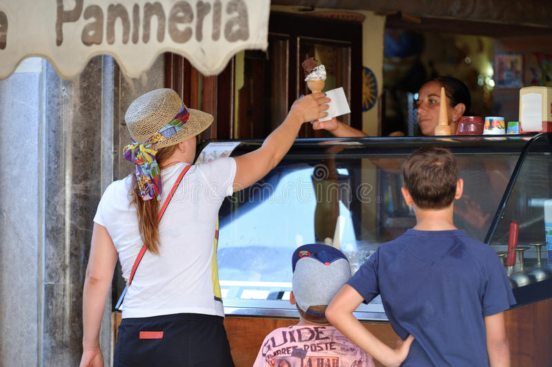 PALERMO, ITALY - AUGUST, 2015: Young woman buying ice cream in the old city center of Palermo in Palermo, Sicily, August, 2015. stock photo