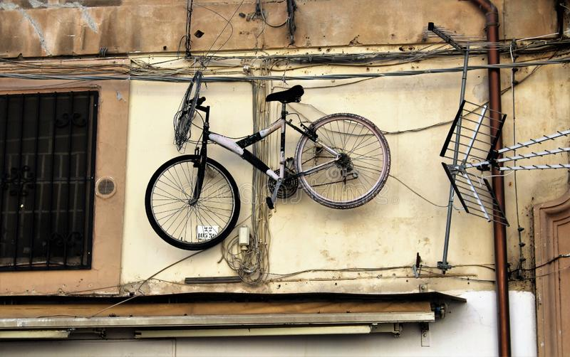 Palermo, Italy - October 16, 2016: mountain bike bicycle hanging on a street wall. Palermo, Italy - October 16, 2016: funny image of a mountain bike bicycle stock photography
