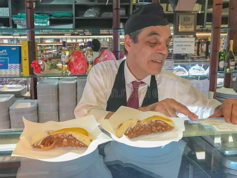 Palermo Sicily Włochy Czerwiec 26, 2018: Męski sprzedawca w ciasto sklepie Sklep Tradycyjny Włoski deser - Sycylijski cannoli obraz royalty free