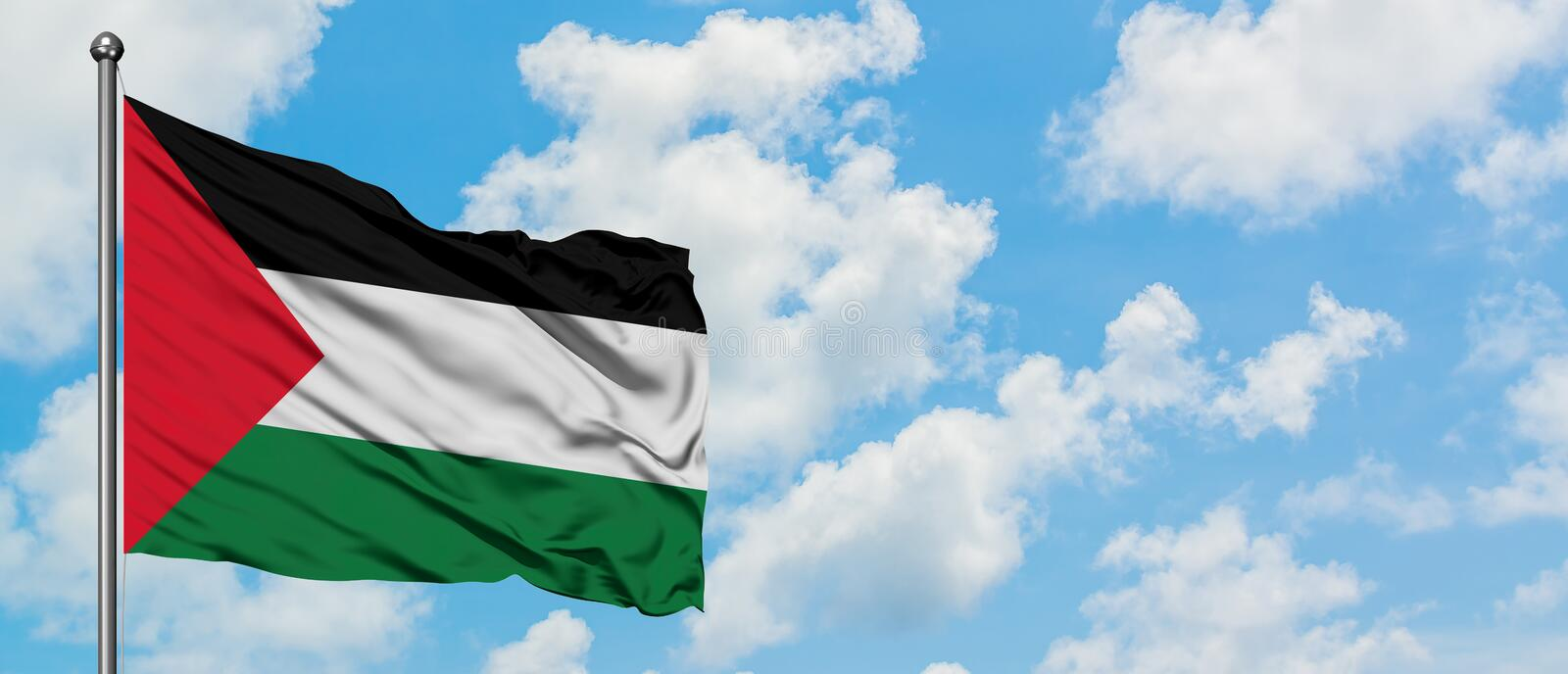 Palestine flag waving in the wind against white cloudy blue sky. Diplomacy concept, international relations.  stock photo