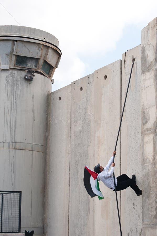Palestinian climbs Israeli separation wall stock photography