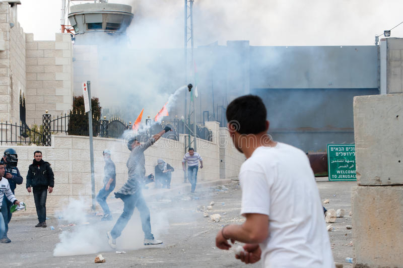 Palestinians throw back tear gas royalty free stock images