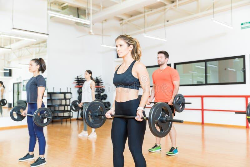 Palestra femminile e maschio di Lifts Barbells In dell'atleta immagini stock