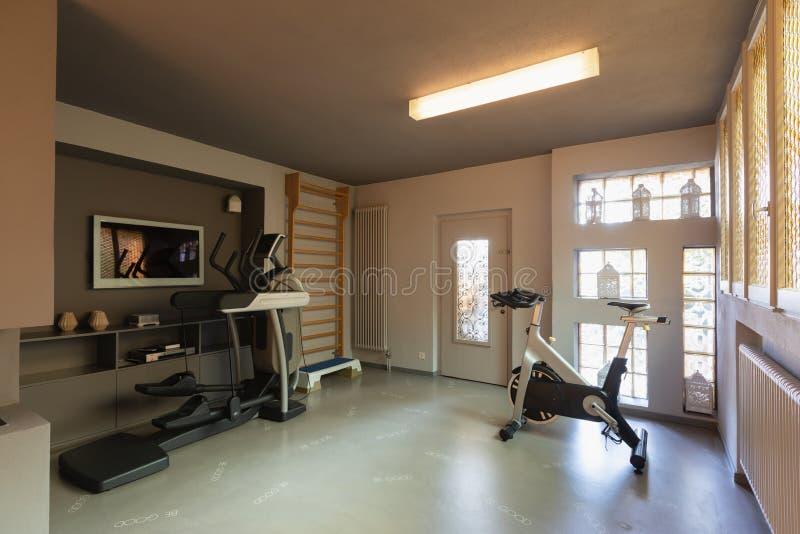 Palestra privata con le bici di esercizio, le pedane mobili e l'albero a spalliera per gli esercizi immagine stock