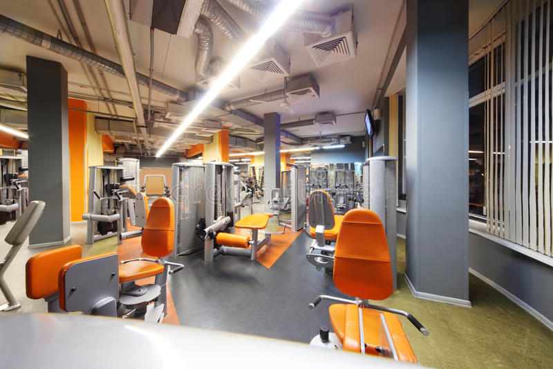Palestra vuota con la strumentazione arancio di esercizio. immagine stock