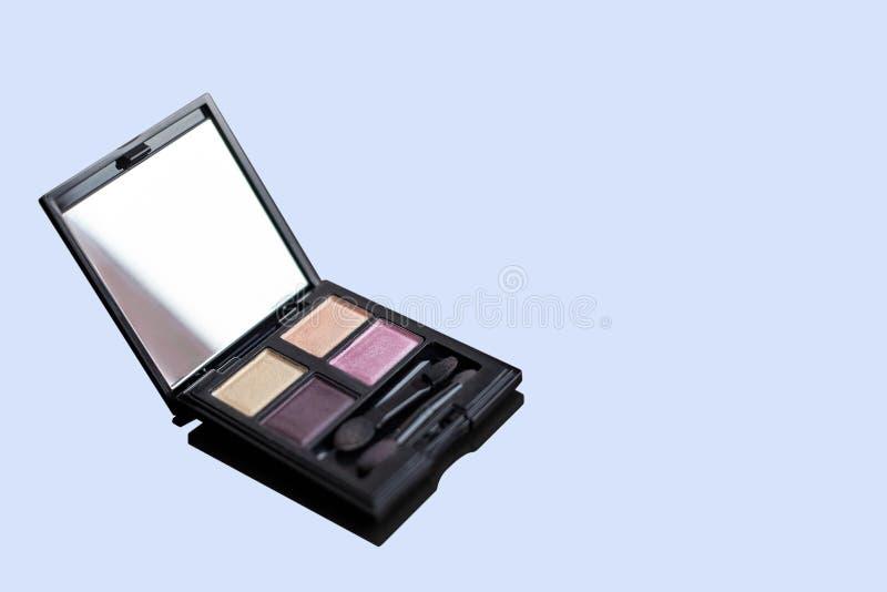 Paleta ascendente próxima da sombra para os olhos, quatro cores em tons lilás, com aplicadores Isolado no fundo azul empoeirado fotografia de stock