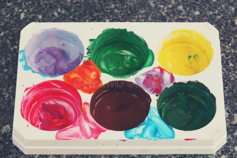 Paleta blanca del arte plástico con la pintura brillante de la acuarela fotos de archivo