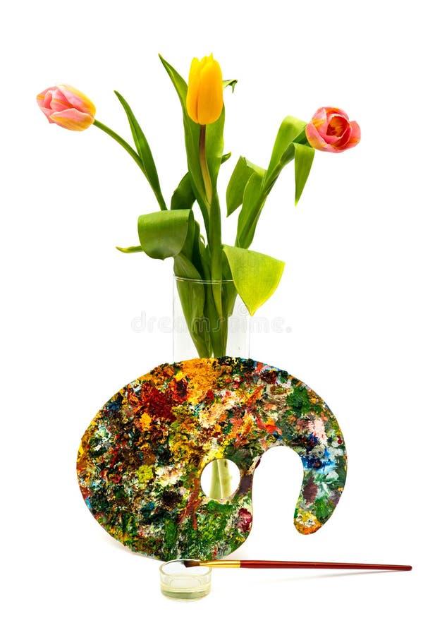 Paleta colorida de la pintura al óleo con un cepillo Brochas y pinturas para dibujar Tulipanes en un fondo blanco imagen de archivo libre de regalías