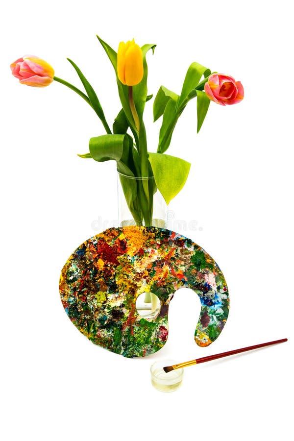 Paleta colorida de la pintura al óleo con un cepillo Brochas y pinturas para dibujar Tulipanes en un fondo blanco fotografía de archivo libre de regalías