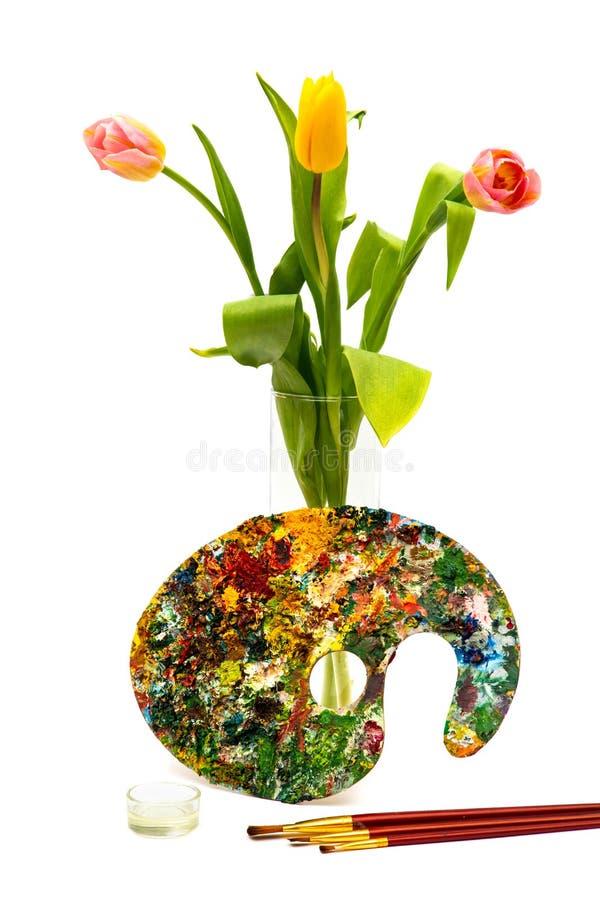Paleta colorida de la pintura al óleo con un cepillo Brochas y pinturas para dibujar Tulipanes en un fondo blanco foto de archivo libre de regalías