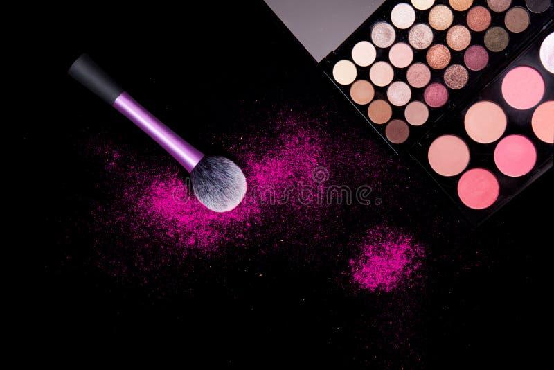 Paleta colorida del maquillaje y cepillo grande rosado para aplicar el polvo en fondo negro puro Equipo profesional del maquillaj foto de archivo