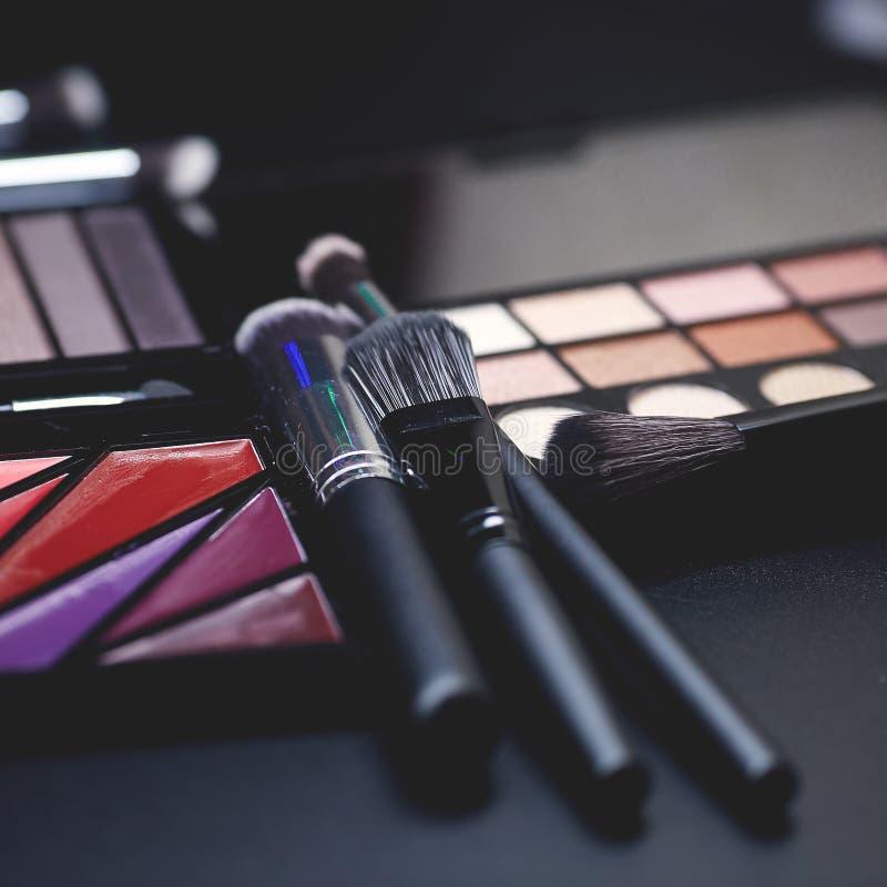 Paleta colorida y cepillo del maquillaje para aplicar el polvo en fondo negro puro imagen de archivo libre de regalías