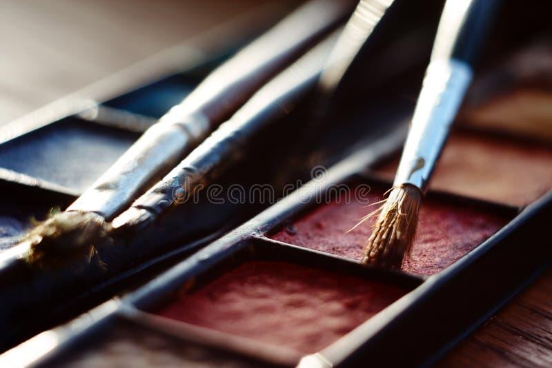 Paleta com pintura da aquarela e escovas de pintura ilustração stock