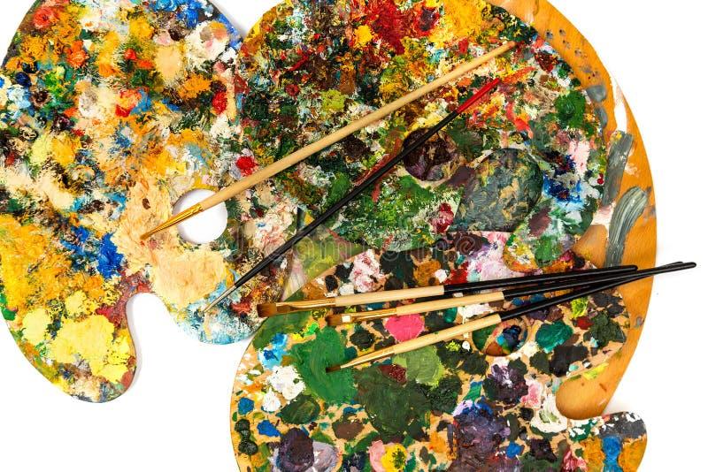 Paleta com pinturas coloridas Paleta colorida da pintura a óleo com uma escova que alcança dentro Tulipa em um fundo branco fotografia de stock royalty free