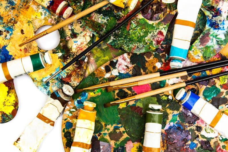Paleta com pinturas coloridas Paleta colorida da pintura a óleo com uma escova que alcança dentro Tulipa em um fundo branco imagem de stock royalty free