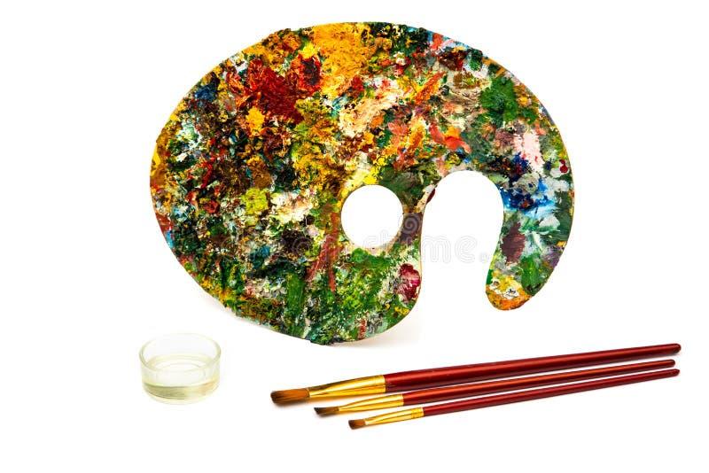 Paleta com pinturas coloridas Paleta colorida da pintura a óleo com uma escova que alcança dentro Tulipa em um fundo branco fotografia de stock