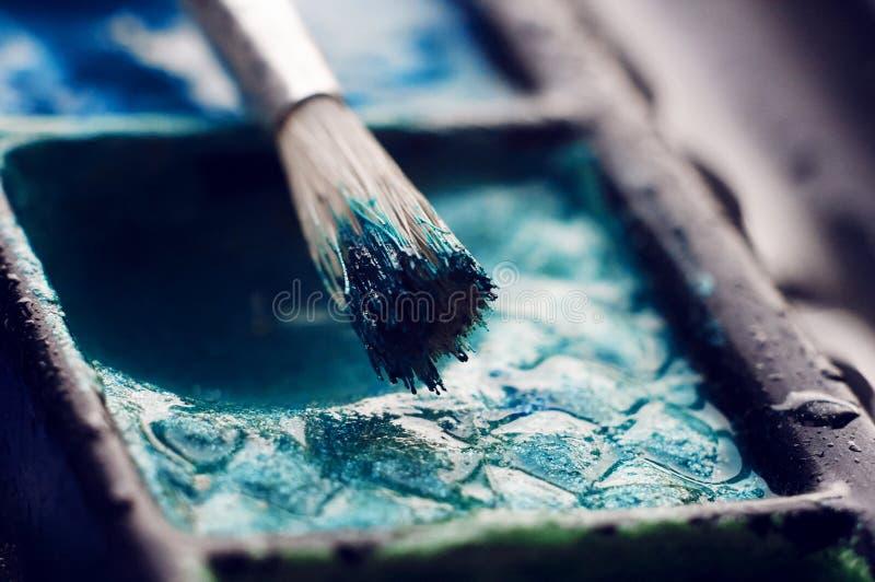 Paleta com uma aquarela brilhante e uma escova fotografia de stock royalty free