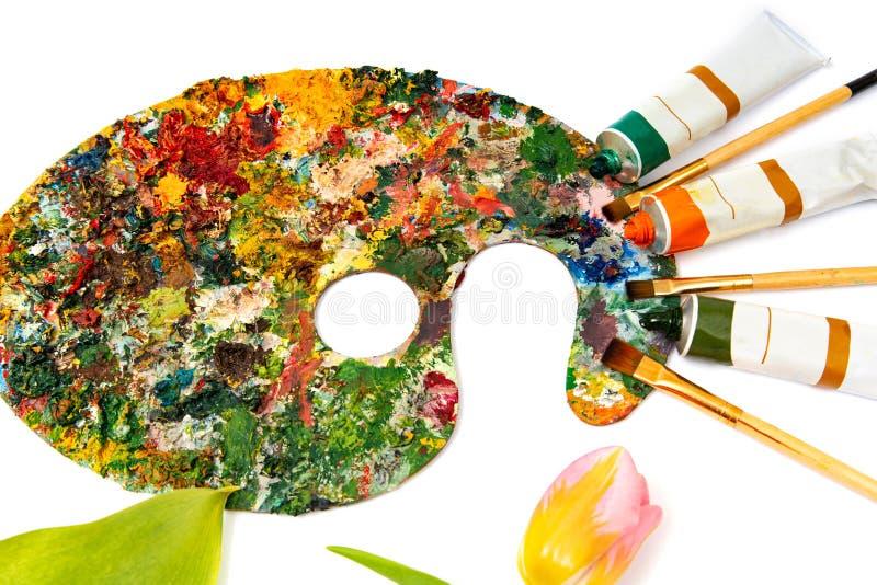 Paleta con las pinturas coloridas Paleta colorida de la pintura al óleo con un cepillo que alcanza adentro Tulipán en un fondo bl foto de archivo