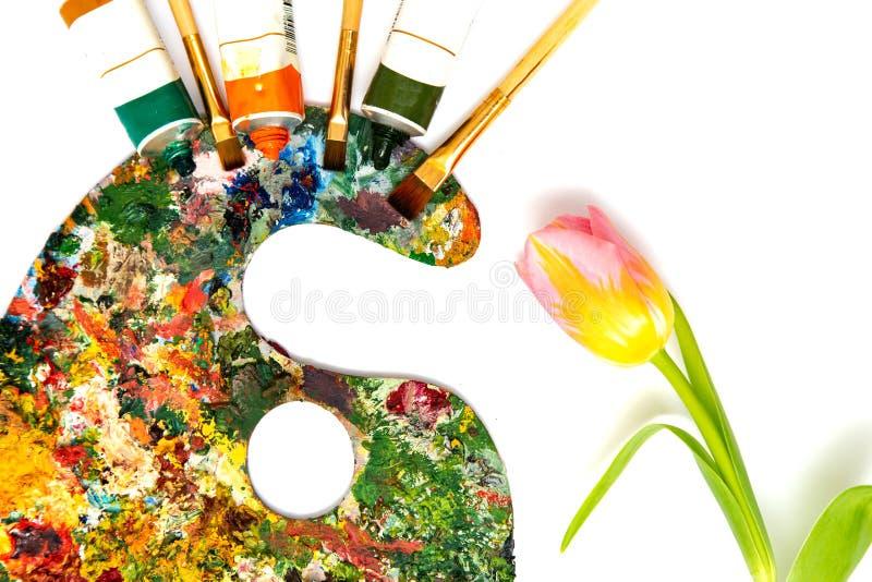 Paleta con las pinturas coloridas Paleta colorida de la pintura al óleo con un cepillo que alcanza adentro Tulipán en un fondo bl imagen de archivo