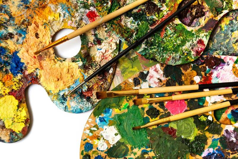 Paleta con las pinturas coloridas Paleta colorida de la pintura al óleo con un cepillo que alcanza adentro Tulipán en un fondo bl fotos de archivo libres de regalías